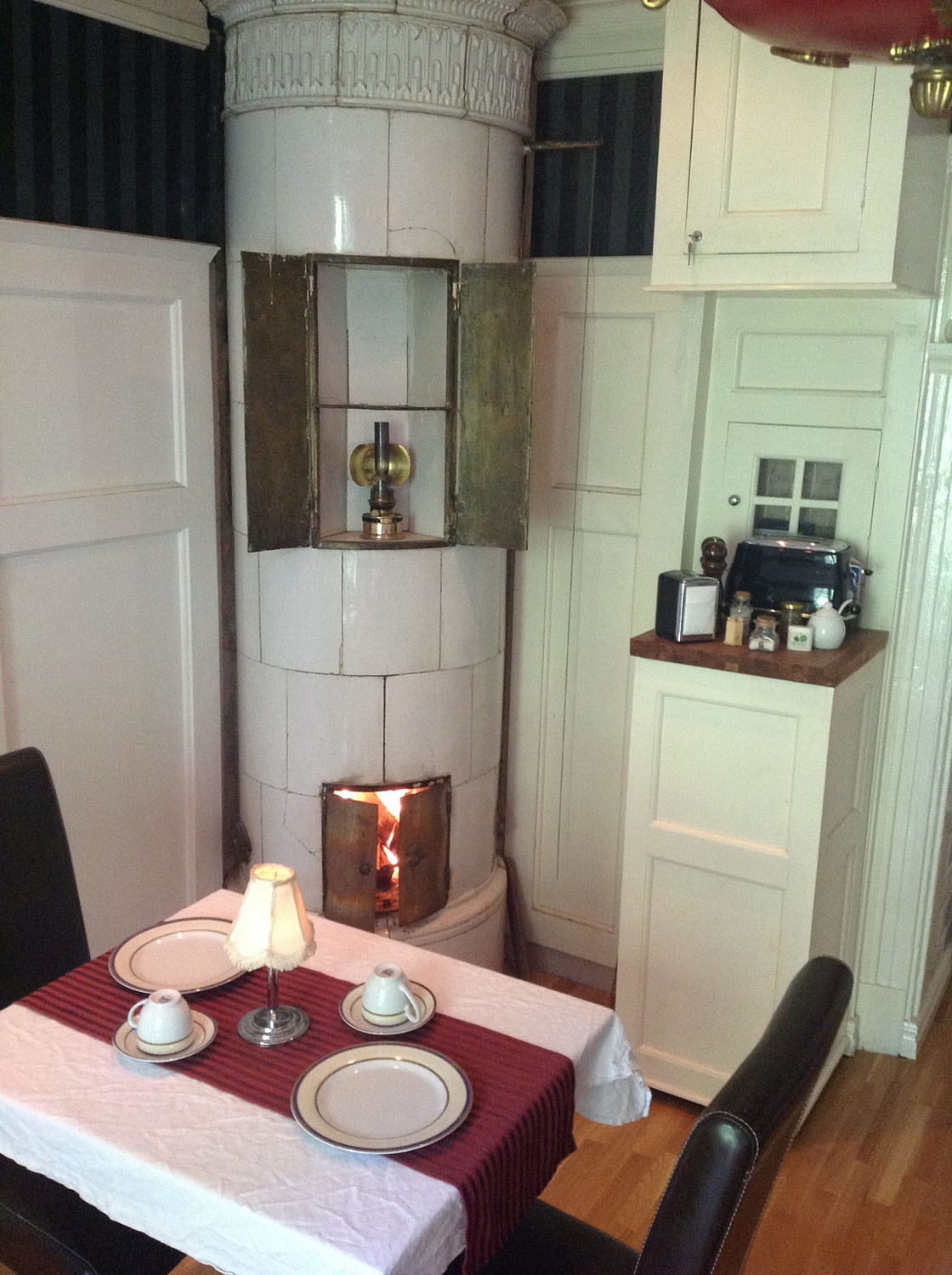Dining hall with fire in tiled stove